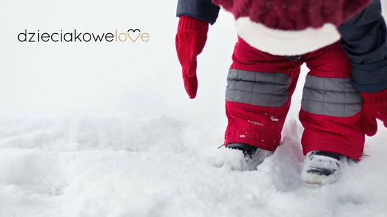 Dziecko w zimowym kombinezonie na śniegu