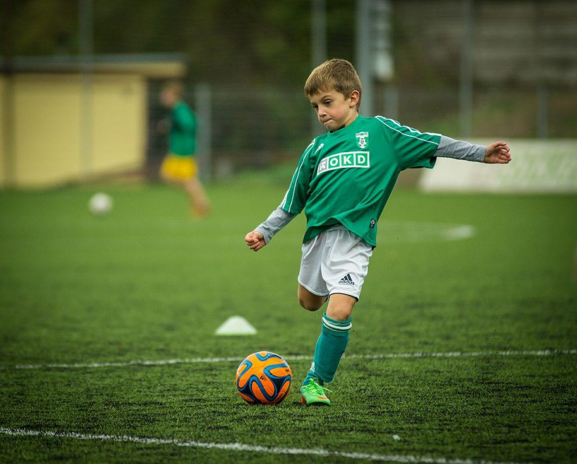 dziecko gra w piłkę nożną w stroju piłkarskim