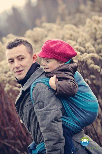 Mężczyzna noszący dziecko w chuście